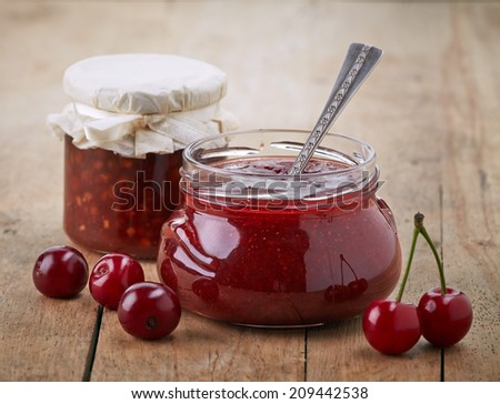 two jars of fruit jam with cherries on wooden table - stock photo