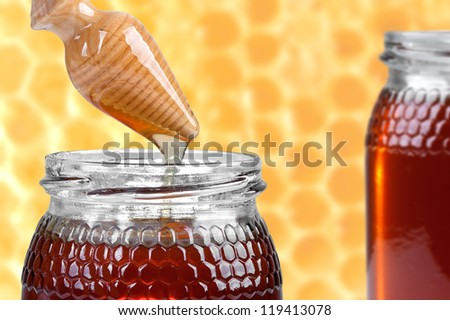 two jars of honey, and wooden drizzler on honeycombs background - stock photo