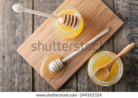Two jars with honey, dipper and wooden spoon on a cutting board. Top view. - stock photo