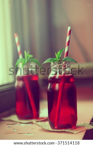 Two jars with organic raspberry juice, placed on a burlap coasters with two striped red and white drinking straws and fresh mint leaves in it, placed on a restaurant table next to a window - stock photo
