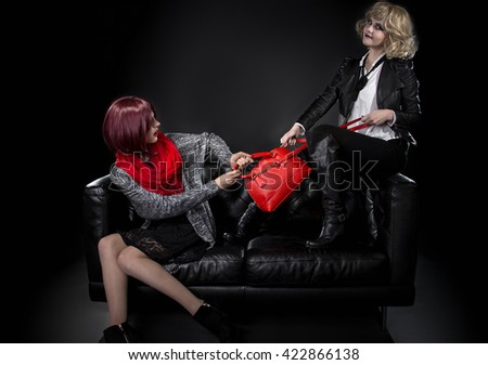 Two jealous fashionable women fighting over red hand bag on a black couch.  They are pulling and tugging on the purse because of envy. - stock photo