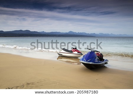 Two jet skis on the beach on an overcast day - stock photo