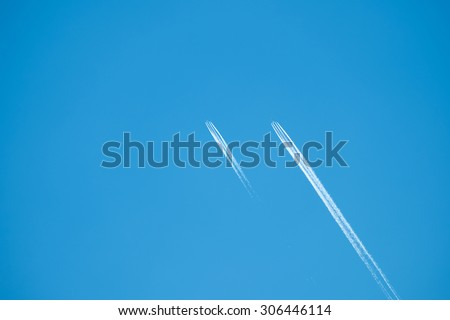 Two jets flying with smoky streams trailing behind - stock photo