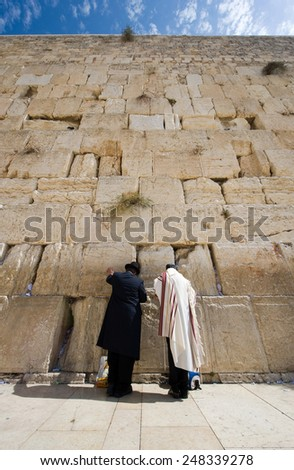 Two jewish men are praying in front of the western wall in the old city of Jerusalem - stock photo