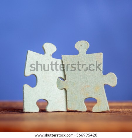 Two jigsaw puzzle pieces on a table joint together. Shallow depth of field
