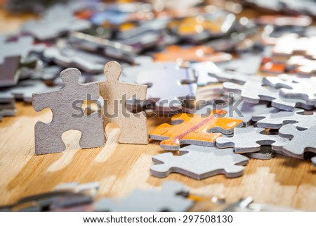Two jigsaw puzzle pieces side by side on a table . Shallow depth of field - stock photo