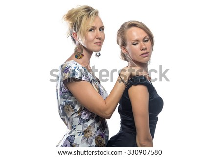 Two joking sisters on white background. Isolated photo on white background.