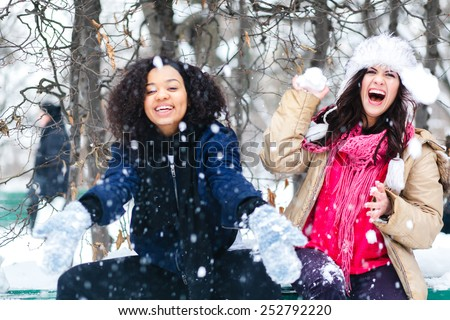 Two joyful and energetic friends playing games and having fun, having a snow ball fight in the snow mountains landscape during a skiing holiday on a sunny winter day, outdoors. snowballs - stock photo