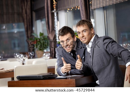 Two joyful businessmen at restaurant celebrate the transaction - stock photo