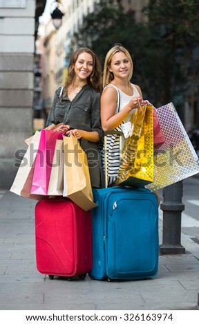 Two joyful girls with suitcases and shopping bags standing in the street
