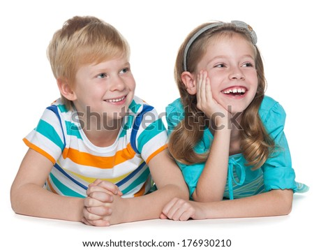 Two joyful redhead children are lying together on the white background