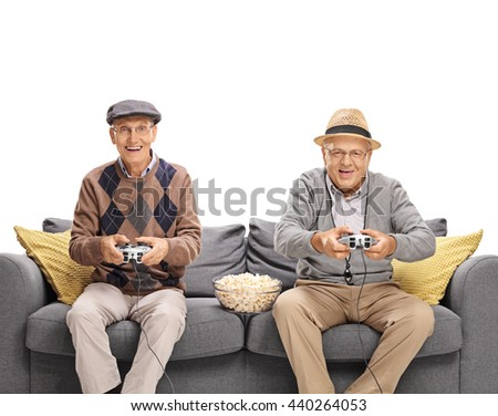 Two joyful seniors playing video games seated on a gray sofa isolated on white background