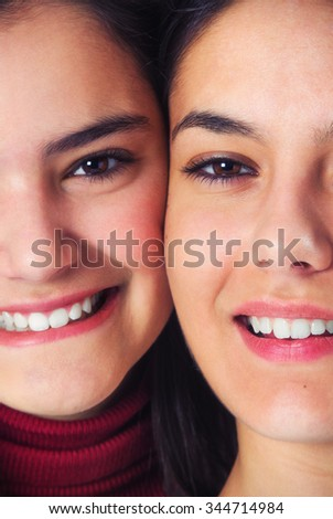 Two joyful teenager girl friends smiling with their heads together - stock photo