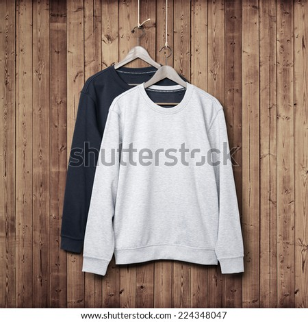 Two jumpers on a dark wood wall
