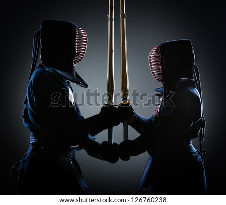 Two kendoka opposite each other with wooden sword. Japanese martial art of sword fighting - stock photo