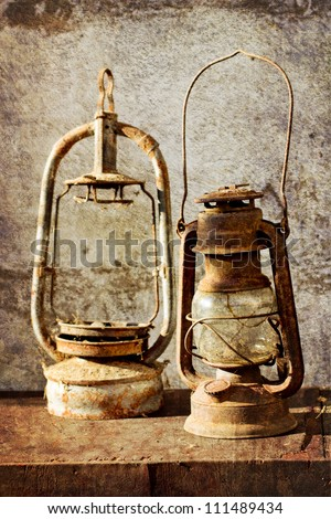 Two kerosene lamps on old table  with grunge texture - stock photo