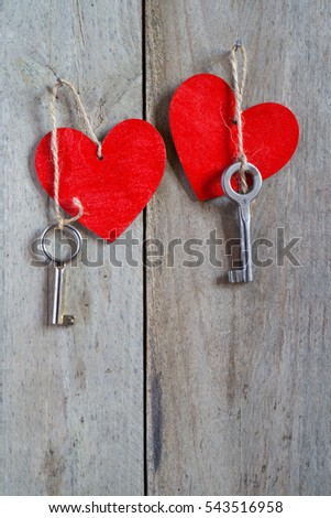 Two keys tied to a red heart with a string. Wooden background