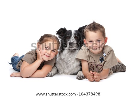 Two kids and a border collie sheepdog in front of a white background - stock photo