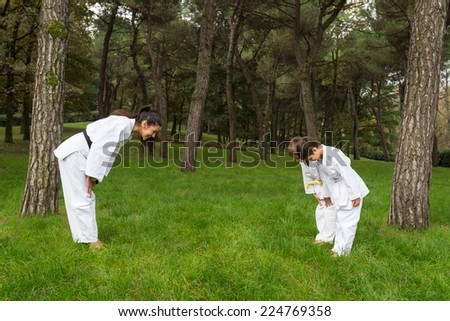 Two kids and master practicing judo outdoors in a park. - stock photo