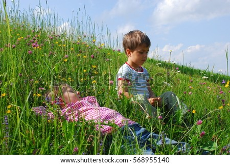 Two kids are sitting and lying in tall grass on meadow in summer enjoying life