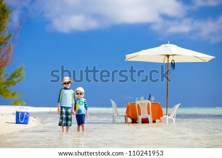 Two kids at picnic with table set in a shallow water near tropical beach