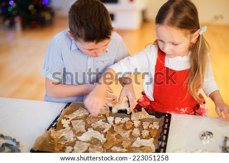 Two kids baking gingerbread cookies at home on Christmas eve - stock photo