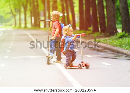 two kids boy and girl-brother and sister- riding scooters in the city - stock photo