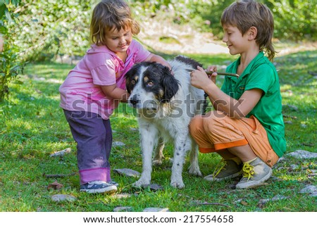 two kids - boy and girl - with dog outdoors - stock photo