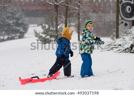 Two kids, boy brothers, sliding with bob in the snow, wintertime, happiness concept