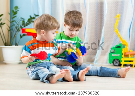 two kids boys play together with educational toys - stock photo