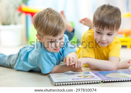 Two kids boys reading a book together - stock photo