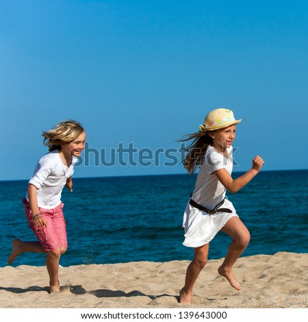 Two kids chasing each other on sunny beach. - stock photo