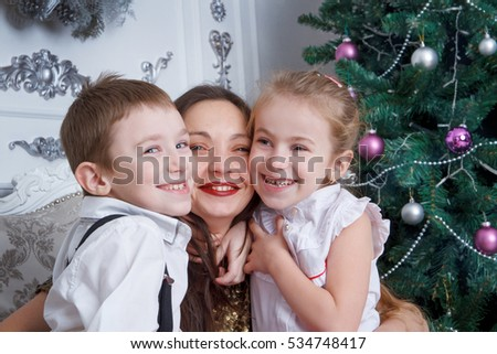Two kids cheek to cheek with their mother under Christmas tree