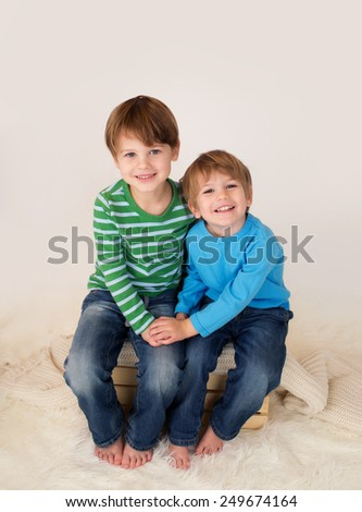 Two kids (children, brothers, siblings), laughing, hugging and looking at the camera holding hands