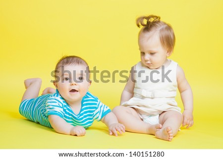 Two kids crawling, isolated on yellow
