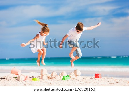 Two kids crushing sandcastle on summer vacation - stock photo