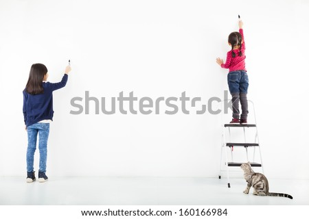two kids drawing on the blank white wall  - stock photo