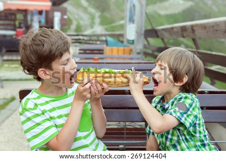 Two kids eat a long french bread in summer outdoor cafe - stock photo