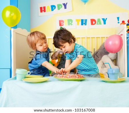 Two kids eating birthday cake at the party - stock photo