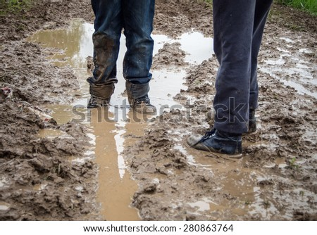Two kids exploring a muddy forest road - stock photo