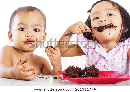 Two kids feasting a plate of chocolate cake.