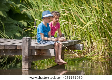 two kids fishing in a river, sitting on a wood pontoon - stock photo