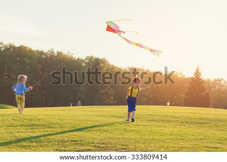 Two kids flies a kite over sunset in park - stock photo