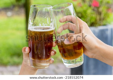 two kids hands toasting with their drinks, shallow depth of field - stock photo