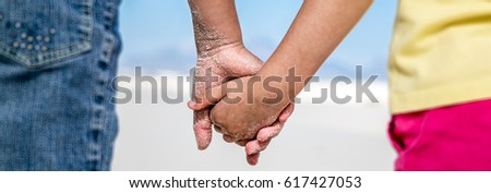 Two kids holding hands in the desert.