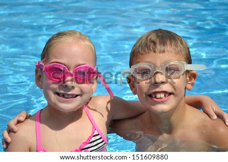 two kids in a swimming pool smiling - stock photo