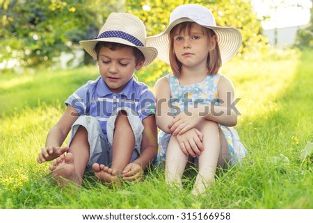 Two kids in hats sitting in park on grass - stock photo