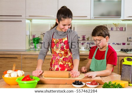 Two kids kneading the dough on table, making the pizza together in the kitchen interior