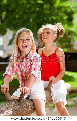 Two kids laughing and swinging on wooden log in park.