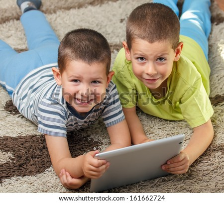 Two kids laying on floor with digital tablet - stock photo